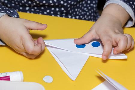 applique: childs hands applique glue boat on yellow desk