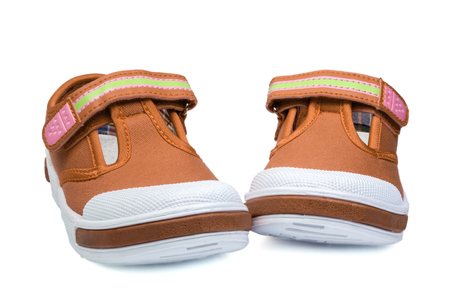 rubber sole: pair of orange child sneakers isolated on white background Stock Photo
