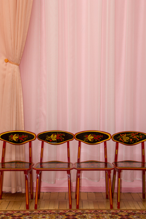 curtain background: pink curtain background with four children chairs Stock Photo