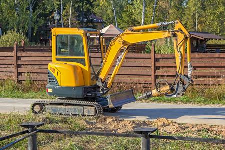 screwing: small yellow crawler excavator for screwing piles Stock Photo