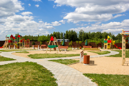 playground equipment: childrens playground with swings and slides countryside Stock Photo