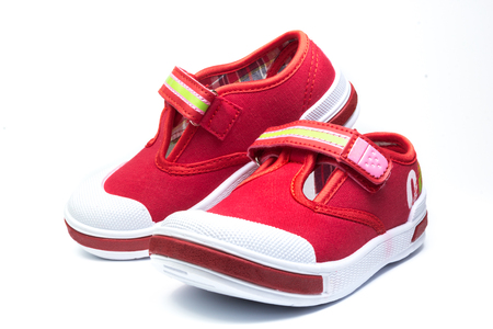 rubber sole: pair of red child  sneakers isolated on white background Stock Photo
