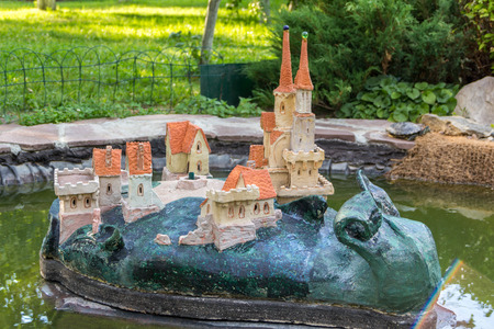 back yard pond: garden statue of a snail with castle on its back in a pond