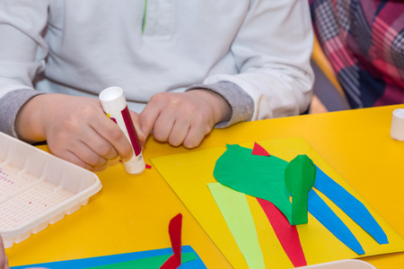 handbreadth: child hands glue colored paper on application master class