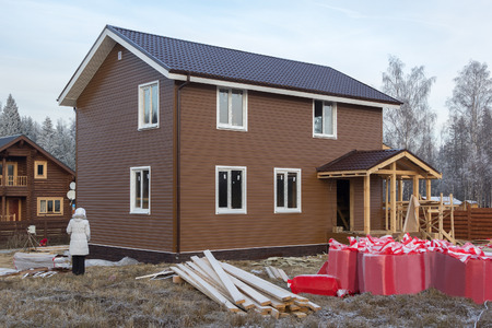 unfinished house trimmed with siding on grass covered with hoarfrost