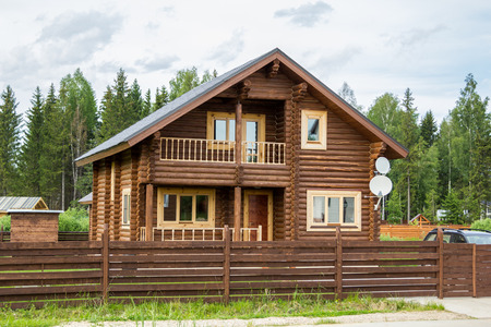 hearthside: brown wooden house behind a wooden fence