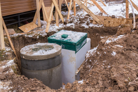 well and a septic tank set in a pit Stock Photo