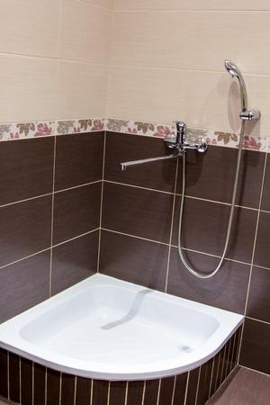 douchebak in de badkamer bekleed met bruin tegels Stockfoto