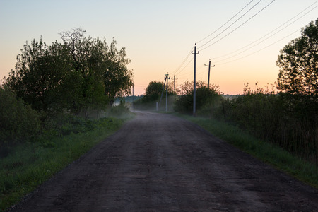 unsurfaced road: Rural dirt road at sunset in the fog