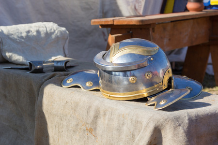 casque: Ancient Roman helmet and ax on the table