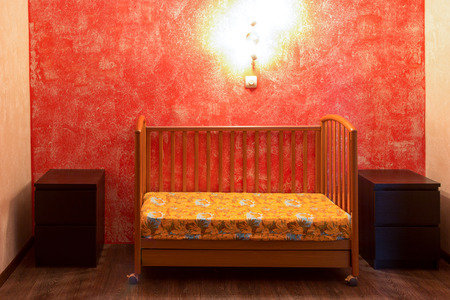 puerile: a cot in the bedroom at the red wall Stock Photo