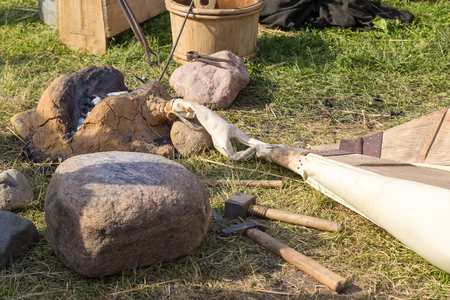 ancient blacksmith: ancient clay forge, furs, hammer, mites and other tools Stock Photo