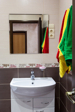interrior: Multicolored towels over the sink in the bathroom