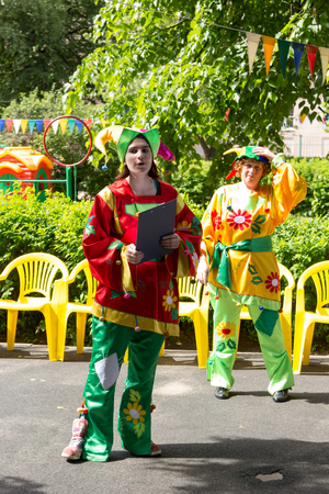 entertain: MOSCOW - JUNE 1, 2015: preschool teacher entertain children in suits of buffoons at the festival