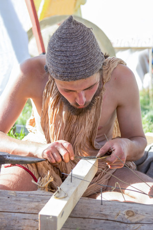 laborious: MOSCOW, RUSSIA - JUNE 7, 2015: Ancient Roman jeweler diligent grinds jewelry at Times and Epochs: Rome historical festival