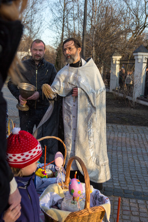 clergyman: MOSCOW - APRIL 11, 2015: Orthodox priest sprinkles Easter eggs and cakes holy water Editorial
