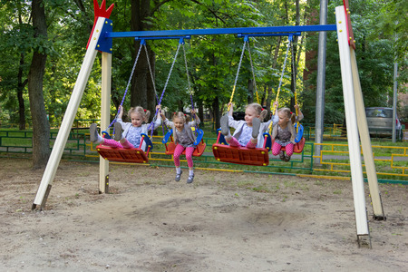 clones: four clones of cute little girl swinging on a swing