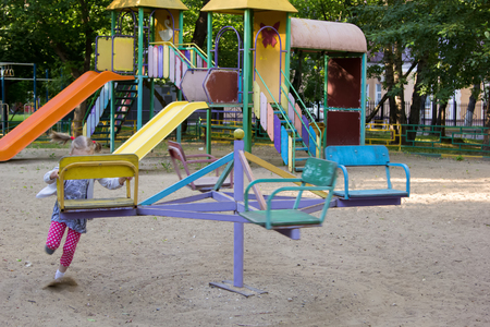 turnaround: little girl spins the carousel at the playground