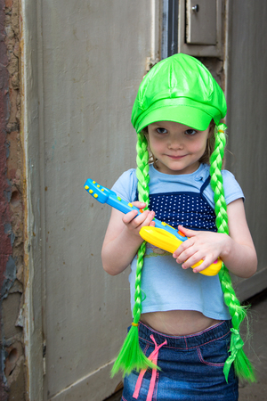 quadrant: little girl rock star in a wig with a guitar Stock Photo