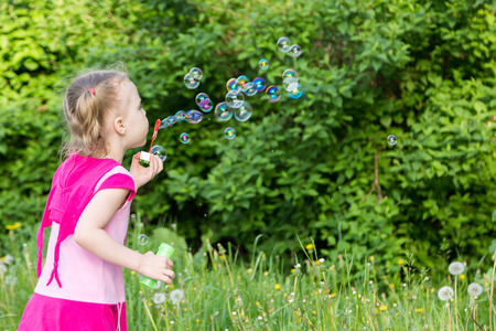 blows: little girl with pigtails blows soap bubbles in park Stock Photo