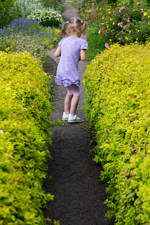 garth: little girl with pigtails on the footpath in the corridor of the bushes