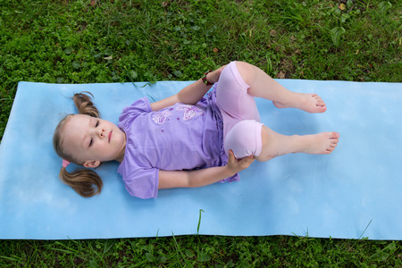 sleeping pad: little girl with pigtails lying on a mat on the grass Stock Photo