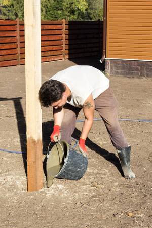 pours: man pours a bucket of cement into a hole