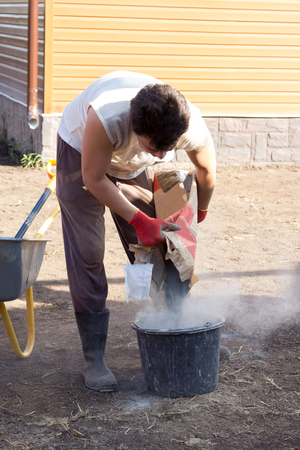 pours: man pours a bag of cement in a bucket Stock Photo
