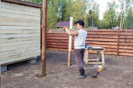 build buzz: man carries a plank to wooden poles