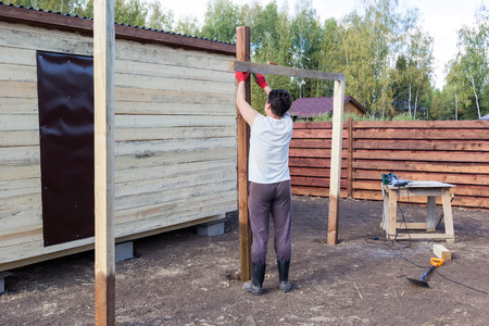 build buzz: man measuring a wooden post on the level Stock Photo