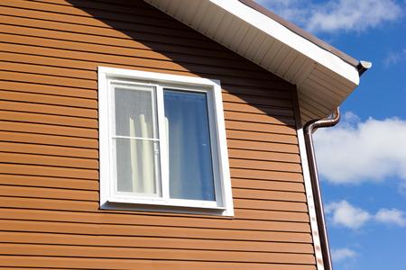 갈색 비닐 사이딩의 벽에 창