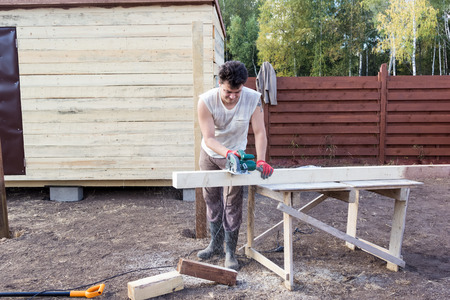 build buzz: man cut the wooden beam with circular saw