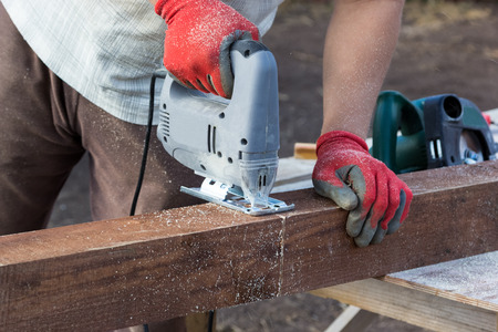 bare wire: man hands cutting the wooden beam with jigsaw