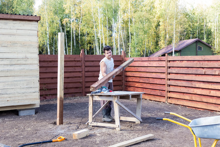 build buzz: man puts a wooden beam on the bench