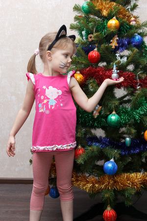 decorates: cat painted little girl decorates the Christmas tree with toys