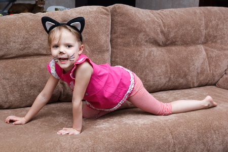 little girl with cat face painting on a couch Stock Photo