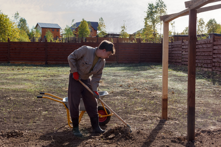 equalize: man leveles the ground with a rake Stock Photo