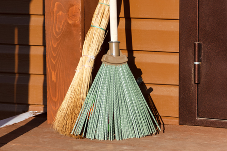 besom: broom and besom standing on the wooden floor Stock Photo