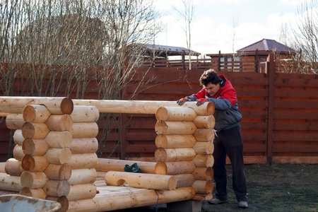 man made structure: man builds a structure made of logs