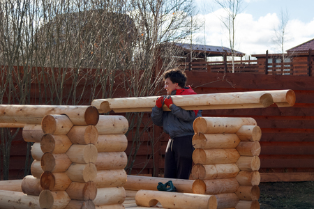 builds: man builds a structure made of logs