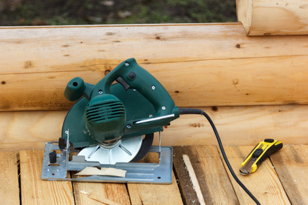 balk: electric circular saw and a knife on a wooden platform