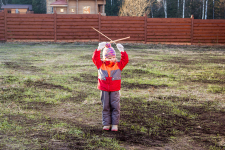 gesticulate: little girl gives signals with two wooden sticks