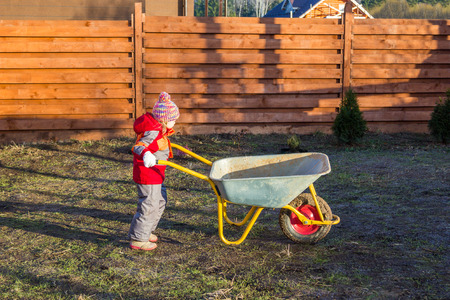 trundle: little girl pushing a garden wheelbarrow Stock Photo