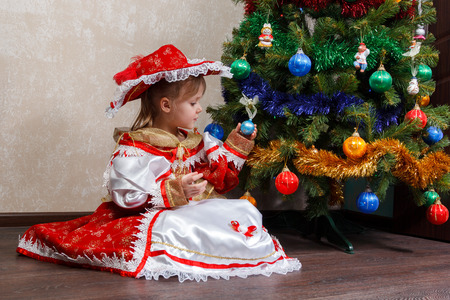 costume ball: little girl in carnival costume holding a Christmas ball