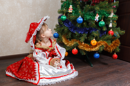 christmas costume: little girl in carnival costume sit near the Christmas tree