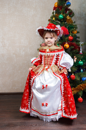 christmas costume: little girl in carnival costume near the Christmas tree Stock Photo