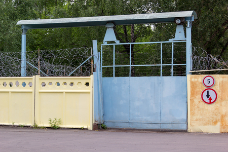 tree works: old metal gate at the entrance to the plant