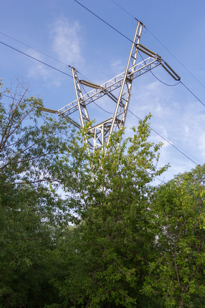 over voltage: tower of high voltage power line over the forest