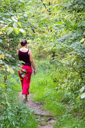 dense forest: woman walking along a footpath in a dense forest Stock Photo