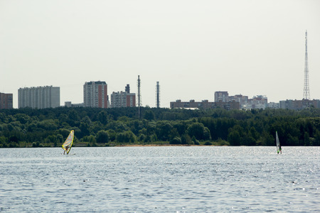 windsurfers: two windsurfers surf in lake in the city Stock Photo
